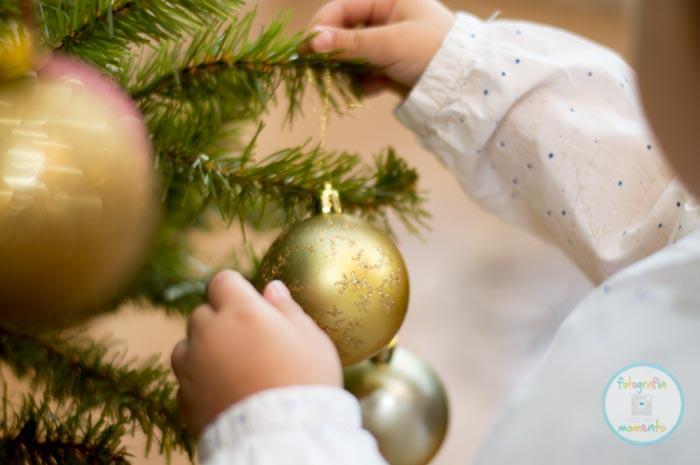niña colgando bola de navidad en un árbol