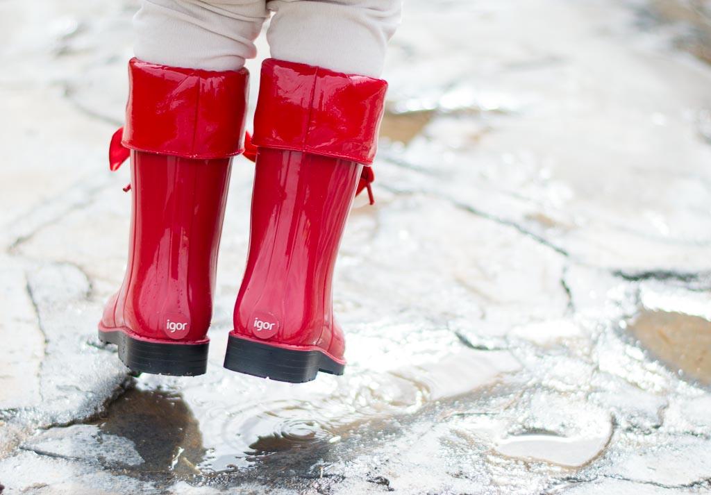 niña saltando charcos con botas de agua rojas