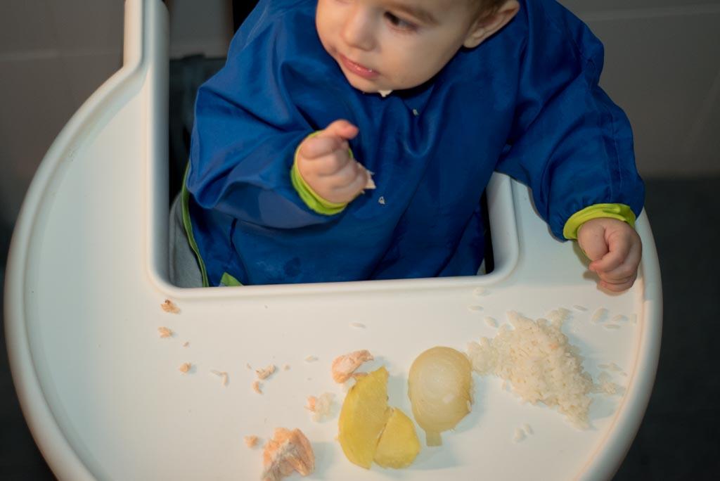 Bebe comiendo patata, arroz y salmon con las manos