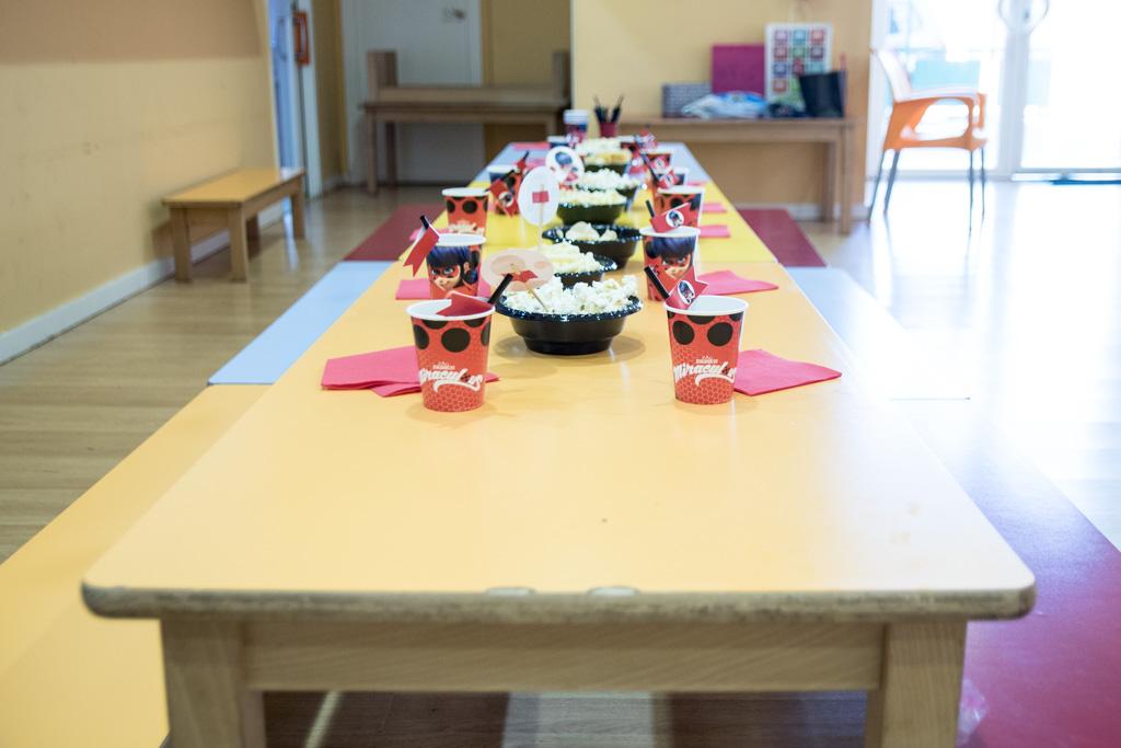 Mesa de cumpleaños de Ladybug con vasos y pajitas temáticas